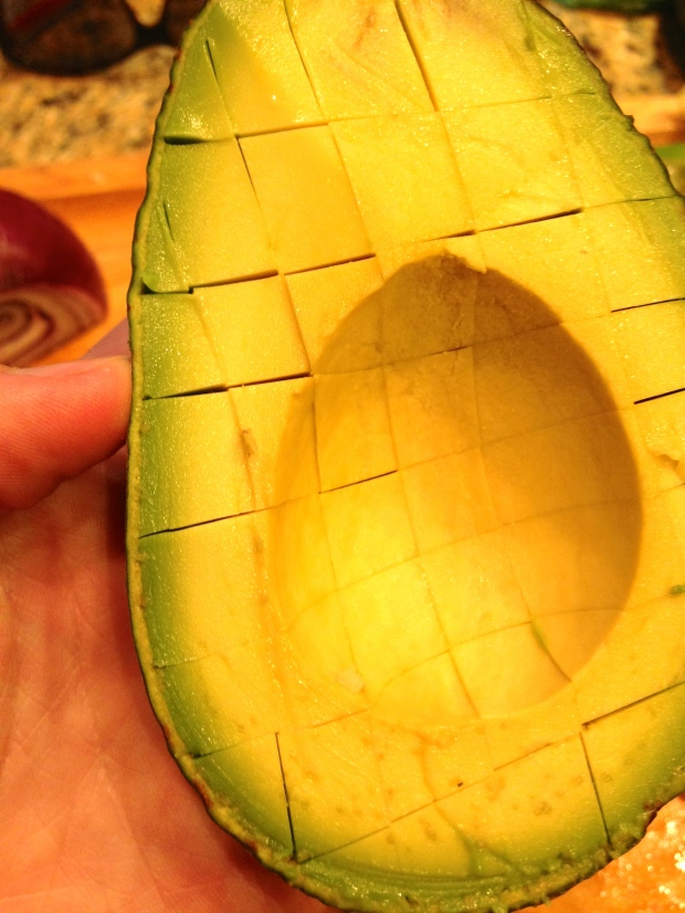 this is how I always cut an avocado for salads, soup toppings etc. — cut it in half, make a grid with a knife, and then scoop it out with a spoon