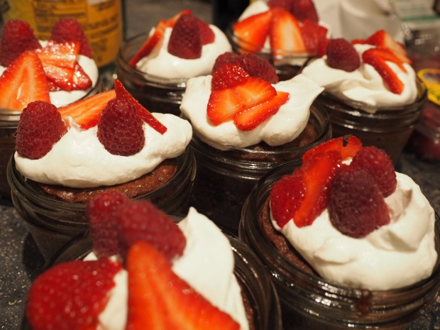 german chocolate cakes in mason jars with fresh berries and whipped cream